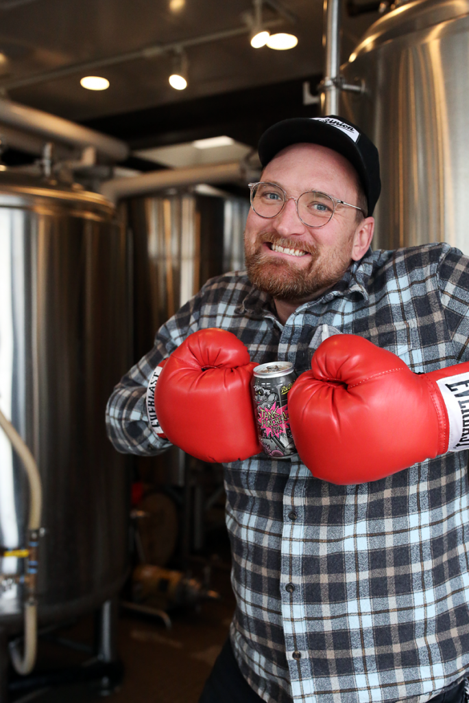 Garret Sorenson standing in brewery with boxing gloves for tank puncher beer